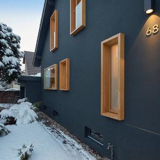 Cette photo montre une façade de maison bleue scandinave à un étage avec un revêtement en stuc.