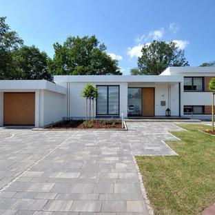 Idéer för ett mellanstort modernt vitt hus i flera nivåer, med stuckatur och platt tak