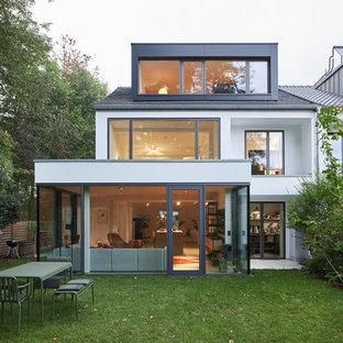 Пример оригинального дизайна: белый таунхаус среднего размера в стиле модернизм с двускатной крышей и черепичной крышей