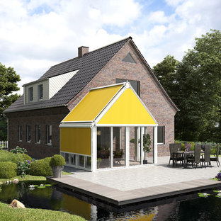 Modelo de fachada de casa marrón, escandinava, de una planta, con revestimiento de ladrillo, tejado a dos aguas y tejado de teja de barro
