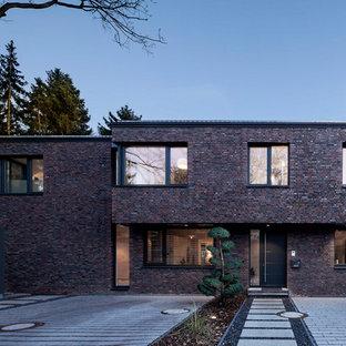Ispirazione per la facciata di una casa unifamiliare multicolore contemporanea a due piani di medie dimensioni con rivestimento in pietra, tetto piano e copertura in metallo o lamiera