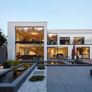 Стильный дизайн: огромный, двухэтажный, белый дом в восточном стиле с облицовкой из бетона и плоской крышей - последний тренд