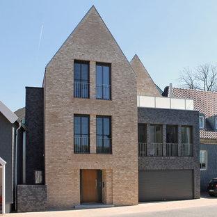 Foto de fachada marrón, actual, de tamaño medio, de tres plantas, con revestimiento de ladrillo y tejado a dos aguas