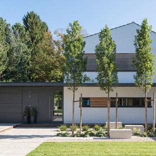 Modelo de fachada blanca, contemporánea, grande, a niveles, con tejado a dos aguas