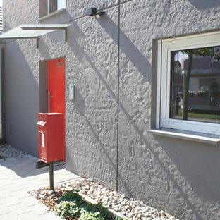 Foto de fachada gris, urbana, extra grande, de dos plantas, con revestimiento de hormigón y tejado a dos aguas