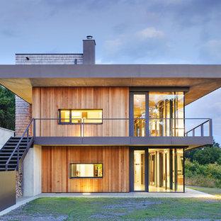 Immagine della facciata di una casa unifamiliare grande marrone contemporanea a tre piani con rivestimento in legno e tetto piano