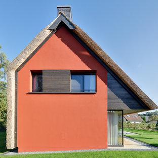 Immagine della facciata di una casa piccola rossa contemporanea a due piani con tetto a capanna e rivestimenti misti