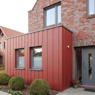Diseño de fachada de casa roja, actual, de tamaño medio, de una planta, con revestimientos combinados, tejado a dos aguas y tejado de teja de barro