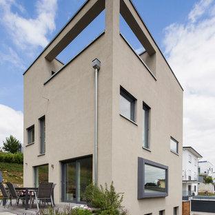 Dreistöckiges, Mittelgroßes, Beigefarbenes Modernes Einfamilienhaus mit Flachdach und Putzfassade in Stuttgart
