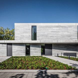Imagen de fachada gris, moderna, de tamaño medio, de dos plantas, con revestimiento de piedra y tejado plano