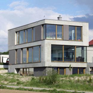 Modelo de fachada de casa gris, contemporánea, de tres plantas, con revestimiento de hormigón, tejado plano y techo verde