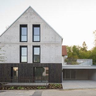 Dreistöckiges, Graues Industrial Einfamilienhaus mit Betonfassade, Satteldach und Blechdach in München