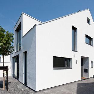 Стильный дизайн: большой, трехэтажный фасад дома белого цвета в современном стиле с двускатной крышей и облицовкой из цементной штукатурки - последний тренд