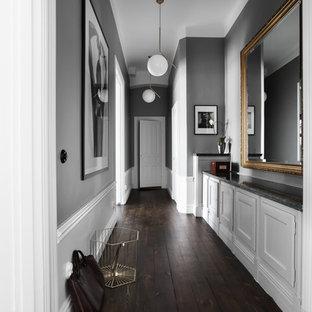 Foto på en nordisk hall, med grå väggar, mörkt trägolv och brunt golv