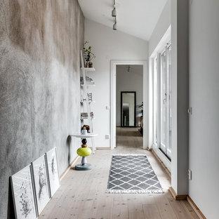 Nordisk inredning av en stor hall, med grå väggar och ljust trägolv