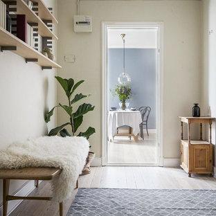 Inspiration för en nordisk hall, med vita väggar och beiget golv