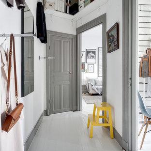 Cette photo montre un couloir scandinave de taille moyenne avec un mur blanc et un sol en bois peint.