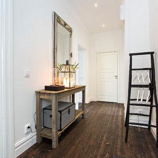 Cette image montre un grand couloir nordique avec un mur blanc et un sol en bois foncé.