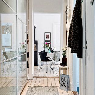 Exempel på en minimalistisk hall, med vita väggar och ljust trägolv