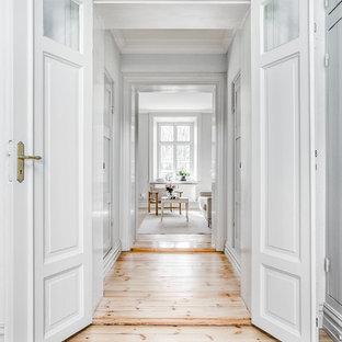 Idéer för stora minimalistiska hallar, med vita väggar och ljust trägolv