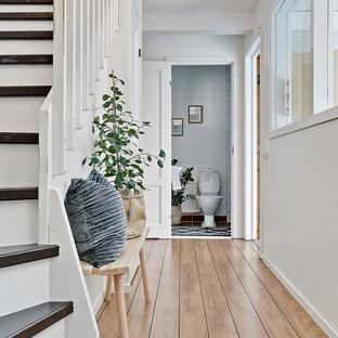 Idéer för en lantlig hall, med vita väggar, ljust trägolv och beiget golv