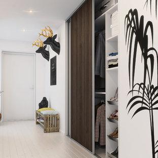 Exempel på en mellanstor modern hall, med vita väggar och målat trägolv