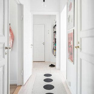 Inspiration för skandinaviska hallar, med vita väggar och ljust trägolv