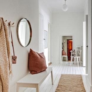 Foto på en liten minimalistisk hall, med vita väggar, målat trägolv och vitt golv