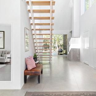 Inspiration för en mellanstor funkis hall, med vita väggar och betonggolv