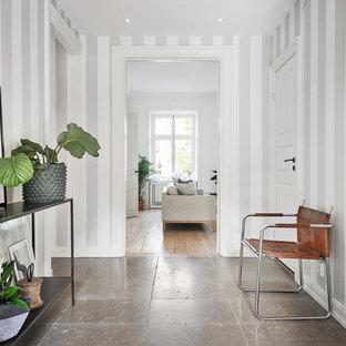 Стильный дизайн: коридор среднего размера в скандинавском стиле с серыми стенами и полом из известняка - последний тренд