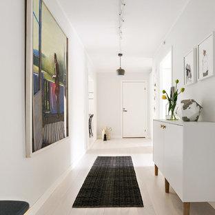 Idéer för att renovera en funkis hall, med vita väggar, ljust trägolv och beiget golv