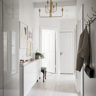 Inredning av en minimalistisk hall, med vita väggar, ljust trägolv och beiget golv