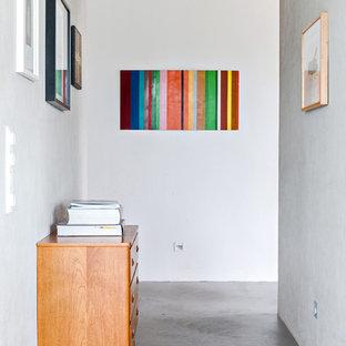 Inspiration för små nordiska hallar, med grå väggar, betonggolv och grått golv