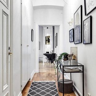 Idéer för att renovera en skandinavisk hall, med vita väggar, mellanmörkt trägolv och brunt golv