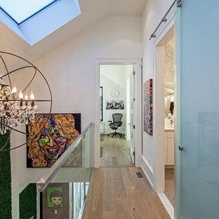 Ispirazione per un ingresso o corridoio boho chic con pareti bianche e pavimento in legno massello medio