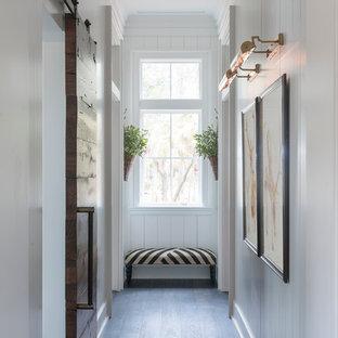 Idées déco pour un couloir campagne de taille moyenne avec un mur blanc, un sol en bois foncé et un sol bleu.