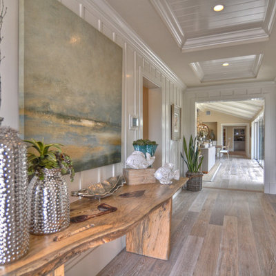 Example of a beach style medium tone wood floor hallway design in Los Angeles with white walls