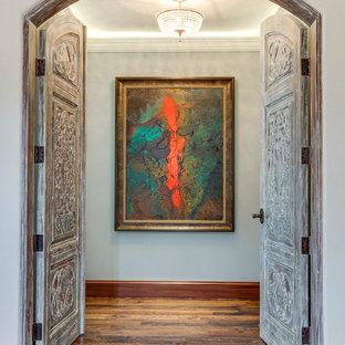 Hallway - mid-sized mediterranean medium tone wood floor hallway idea in Los Angeles with gray walls