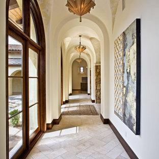 Hallway - mediterranean beige floor hallway idea in Austin with white walls