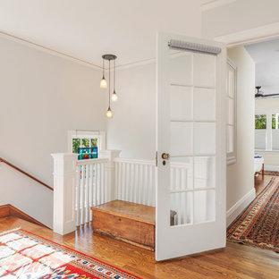 Inspiration pour un couloir craftsman de taille moyenne avec un mur blanc, un sol en bois brun et un sol marron.