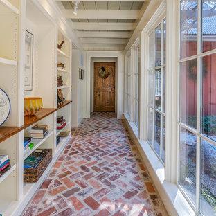 Cette photo montre un couloir nature avec un mur blanc, un sol en brique et un sol rouge.