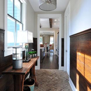 Cette image montre un couloir traditionnel avec un mur beige, un sol en brique et un sol marron.
