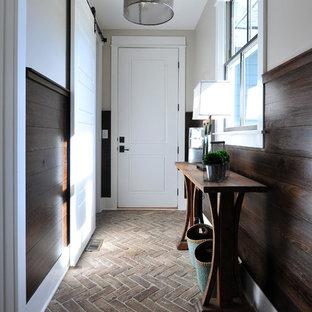 На фото: коридор в стиле неоклассика (современная классика) с бежевыми стенами и кирпичным полом с
