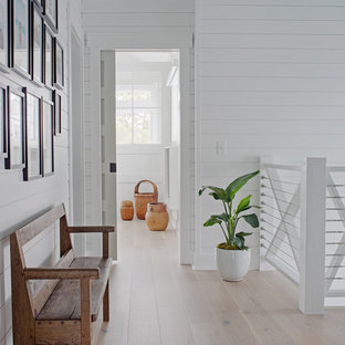 Hallway - small beach style light wood floor and brown floor hallway idea with white walls