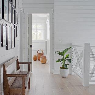 Ejemplo de recibidores y pasillos costeros, pequeños, con paredes blancas, suelo de madera clara y suelo marrón