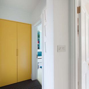 На фото: маленький коридор в стиле модернизм с белыми стенами, ковровым покрытием, черным полом и многоуровневым потолком с