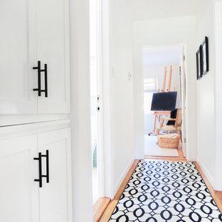 Imagen de recibidores y pasillos modernos, de tamaño medio, con paredes blancas y suelo de madera clara