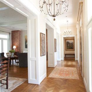 Hallway - large traditional medium tone wood floor hallway idea in Houston with white walls