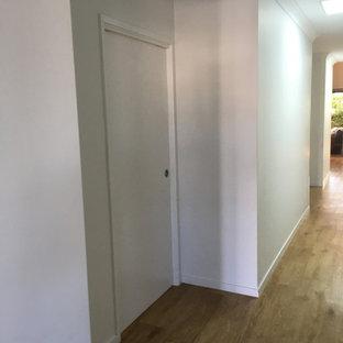 Идея дизайна: большой коридор в современном стиле с белыми стенами, полом из фанеры, коричневым полом, кессонным потолком и панелями на части стены