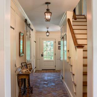 На фото: большие коридоры в классическом стиле с бежевыми стенами, кирпичным полом и красным полом